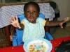 Eden feeding herself rice and veggies